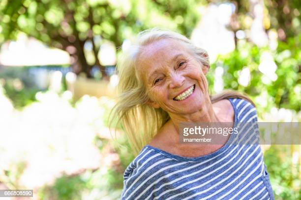 Portrait of smiling, modern, attractive mature woman in sunshine