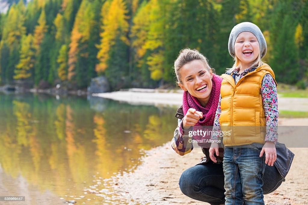 Portrait of smiling mother and baby on lake braiesl, italy : Stock Photo