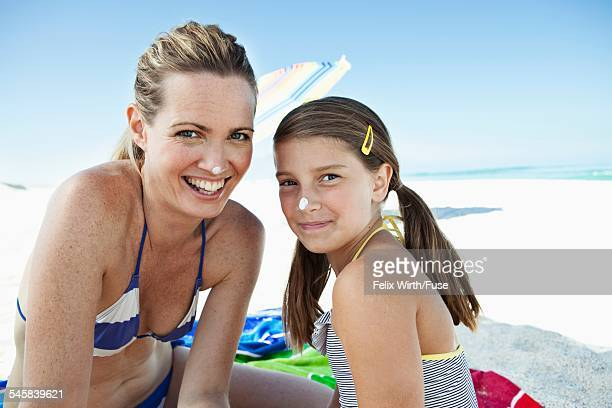 Portrait of smiling mother and daughter (10-12) with sun cream spots on noses