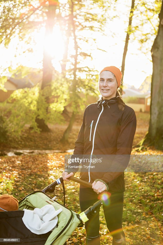 Portrait of smiling mother standing with baby stroller at park