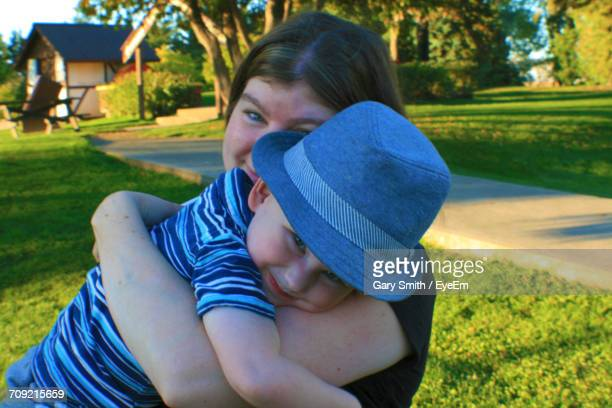 Portrait Of Smiling Mother With Son On Grassy Field
