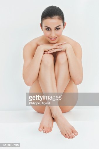 Portrait of smiling nude woman hugging knees : Stock Photo