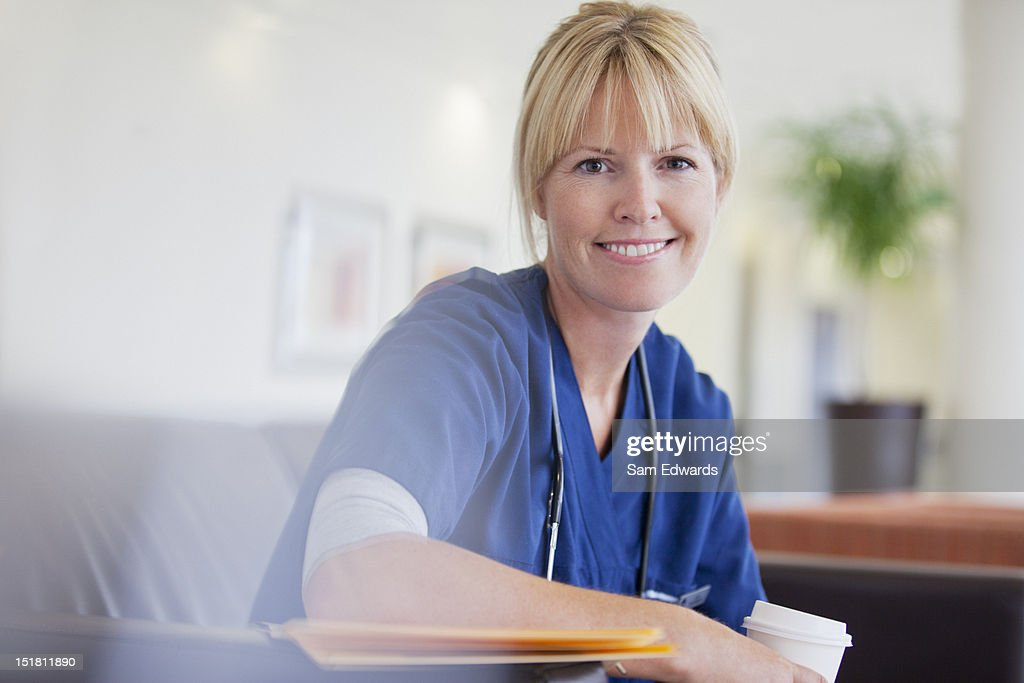 Portrait of smiling nurse drinking coffee in hospital : Stock Photo