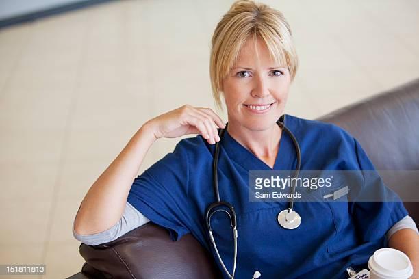 Retrato de la sonriente enfermera bebiendo café