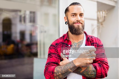 Portrait of smiling owner with coffee outside candy store