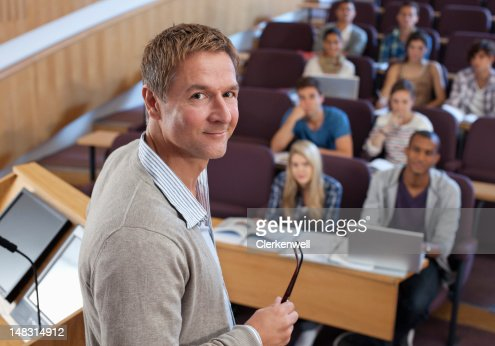 Portrait of smiling professor at podium with university students in background