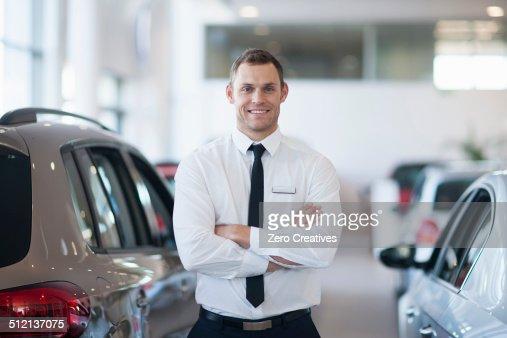 Portrait of smiling salesman in car dealership
