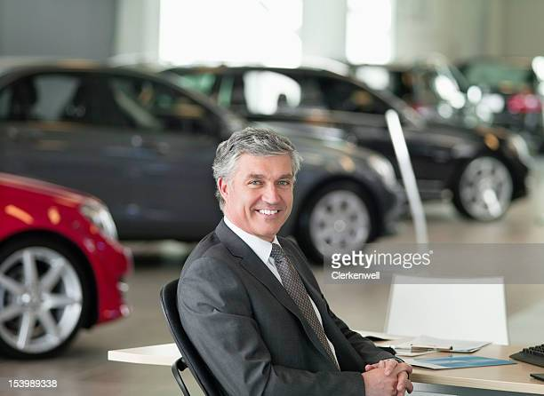 Portrait of smiling salesman sitting at desk in car dealership showroom