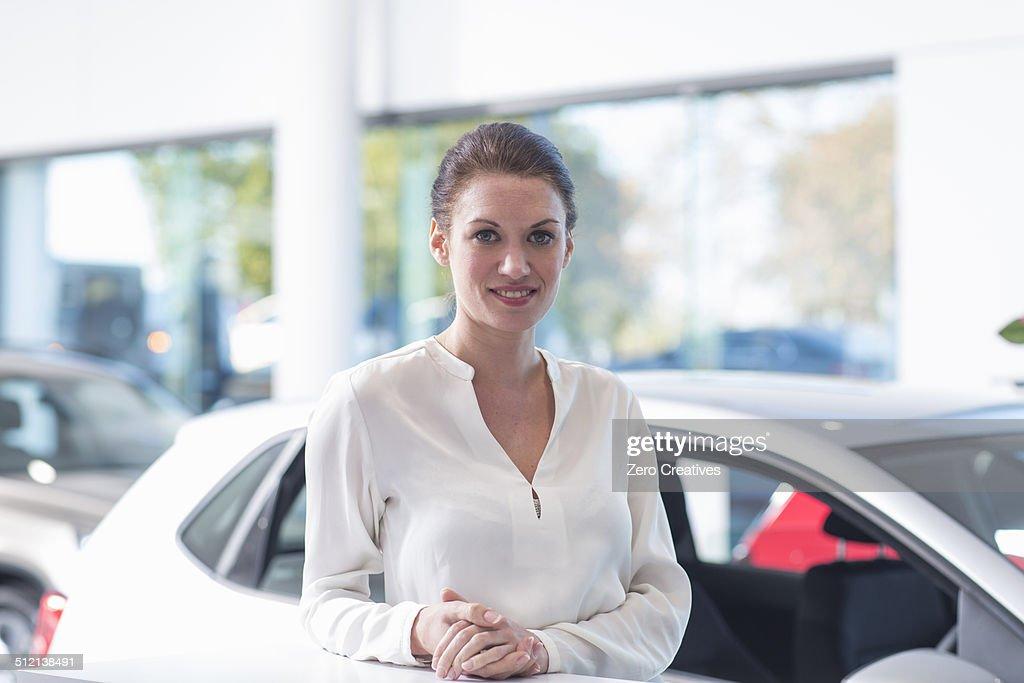 Portrait of smiling saleswoman in car dealership