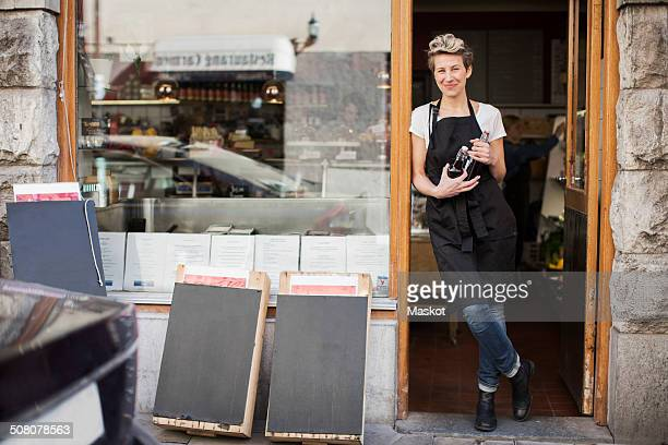 Portrait of smiling saleswoman standing at supermarket entrance