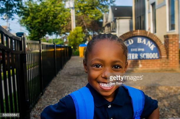 Portrait of smiling schoolboy at school gate