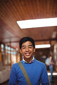 Portrait of smiling schoolboy standing in corridor at school