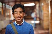 Portrait of smiling schoolboy standing in corridor at school