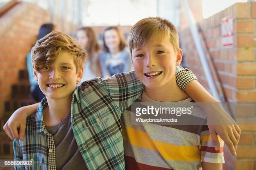 Portrait of smiling schoolboys standing with arm around in corridor : Stock Photo