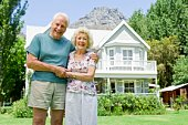 Portrait of smiling senior couple by house