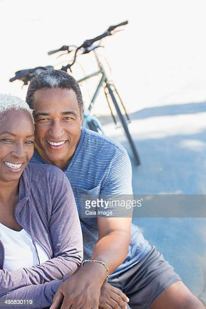 Portrait of smiling senior couple near bicycle
