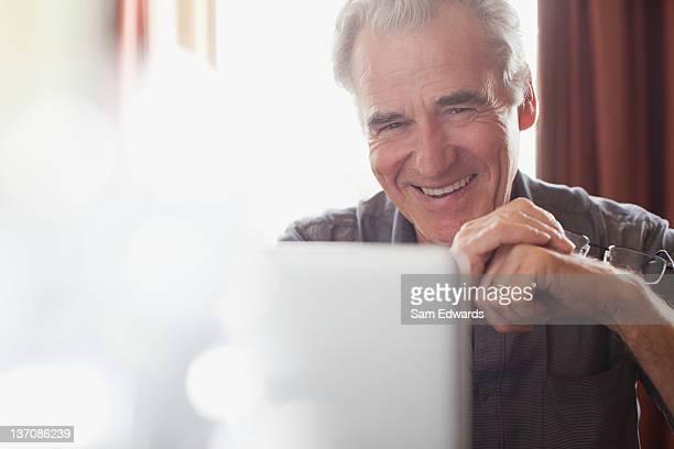 Portrait d'homme senior souriant tenant Lunettes de vue et de l'utilisation d'ordinateur