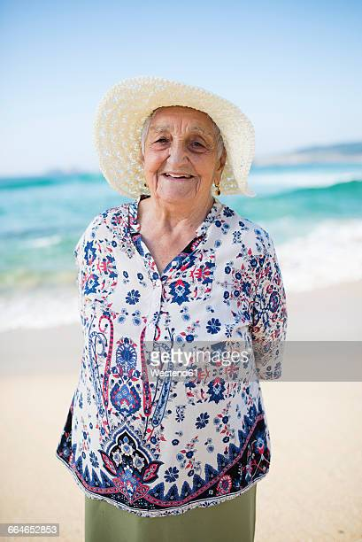 Portrait of smiling senior woman standing on the beach