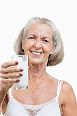 Portrait of smiling senior woman with a glass of milk against white background