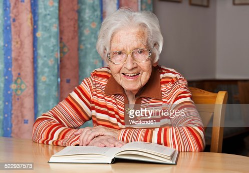 Portrait of smiling senior woman with opened book