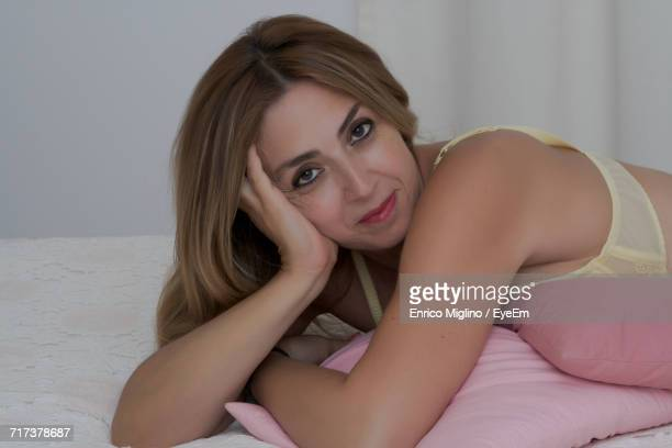 Portrait Of Smiling Sensuous Beautiful Woman Lying On Bed At Home