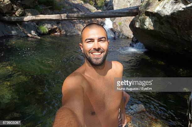 Portrait Of Smiling Shirtless Man Standing On Stream In Forest