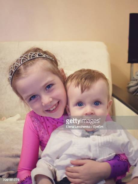 Portrait Of Smiling Sister With Brother On Sofa At Home