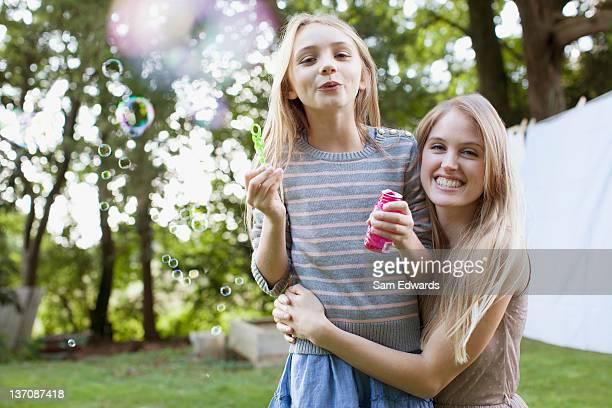 Portrait de souriant sisters envoyer des bulles dans l'arrière-cour