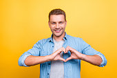 Portrait of  smiling, stunning man with stubble showing heart figure with fingers over yellow background