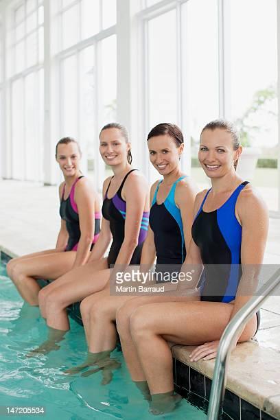 Portrait de souriant les nageurs avec les pieds dans la piscine