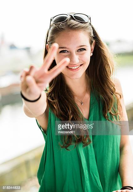 Portrait of smiling teenage girl showing Victory sign