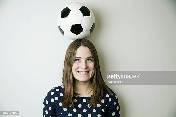 Portrait of smiling teenage girl with football on her head in front of white wall