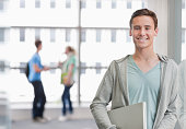 Portrait of smiling university student holding laptop