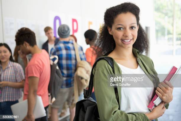 Portrait of smiling university student standing in corridor