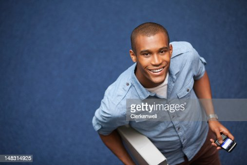 Portrait of smiling university student with cell phone : Stock Photo