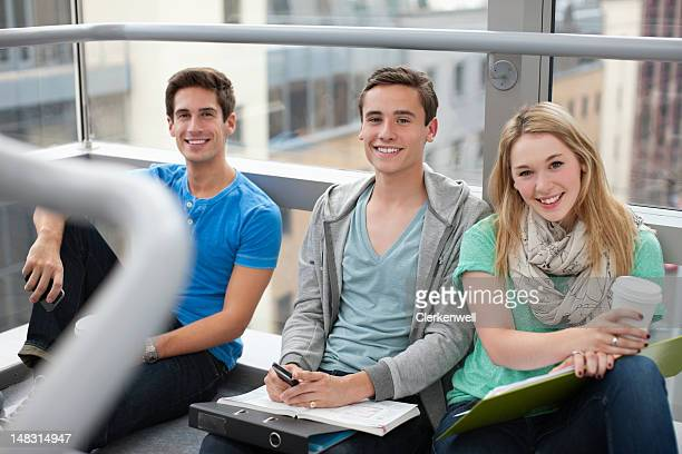 Portrait of smiling university students sitting in window