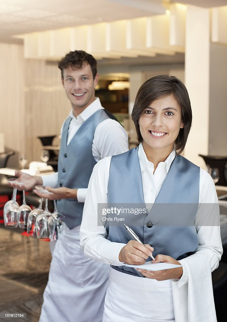 Portrait of smiling waiter and waitress in restaurant : Stock Photo