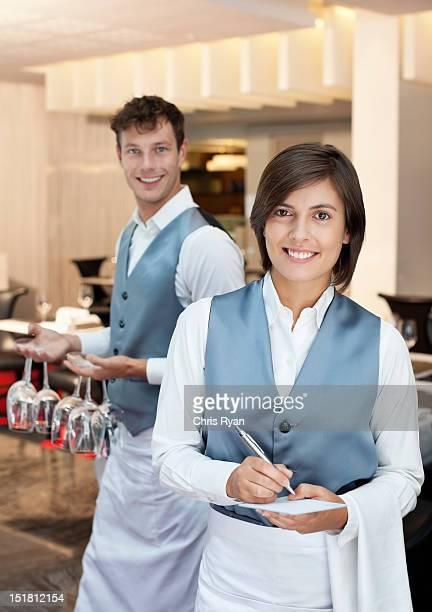Retrato de la sonriente y camarera camarero en el restaurante