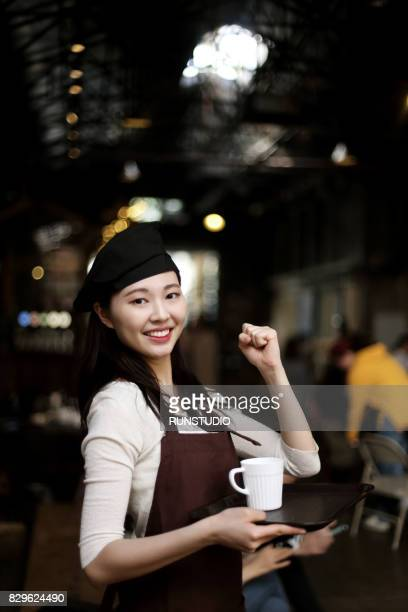 Portrait of smiling waitress with tray