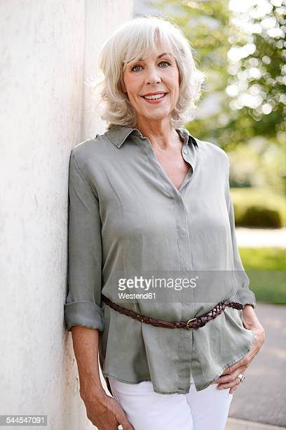 Portrait of smiling white haired senior woman leaning against concrete wall