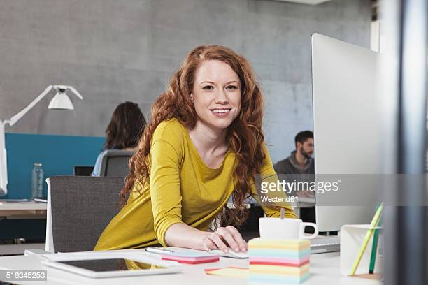 Portrait of smiling woman at her workplace in the open space office