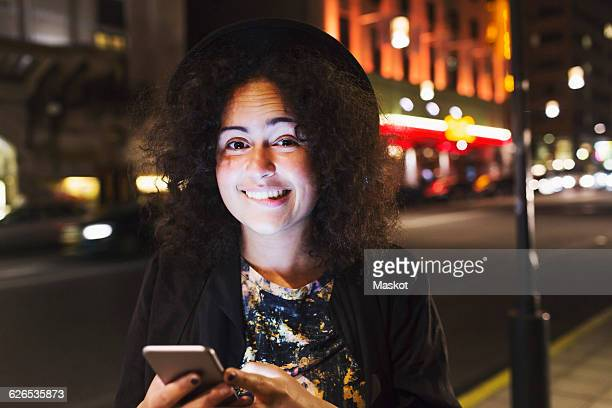 Portrait of smiling woman biting lip while holding smart phone in city at night