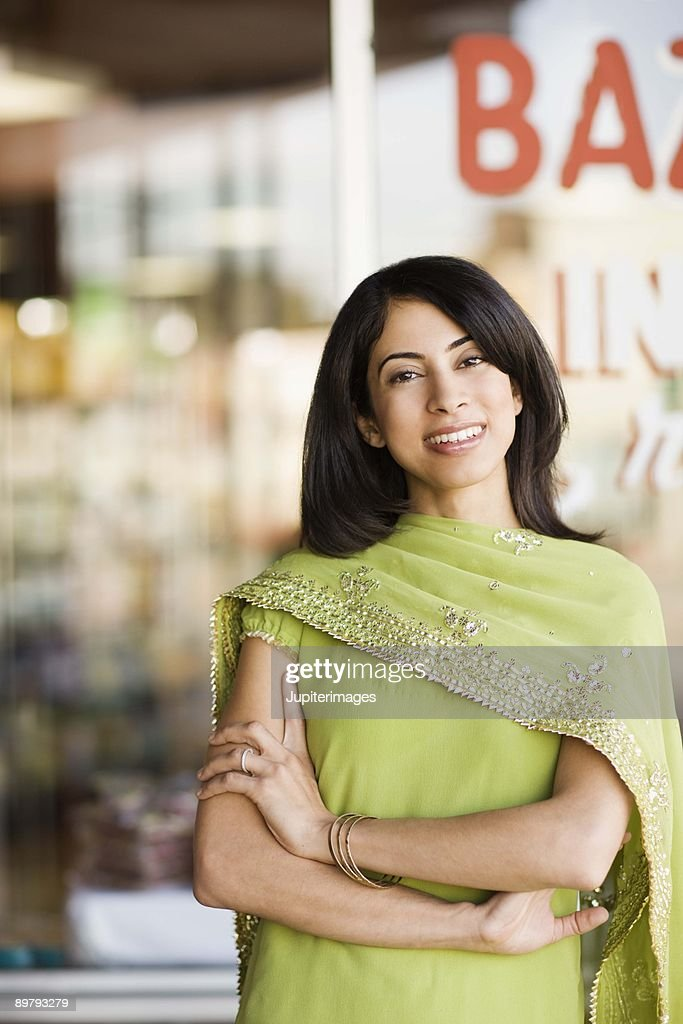 Portrait of smiling woman by storefront : Stock Photo