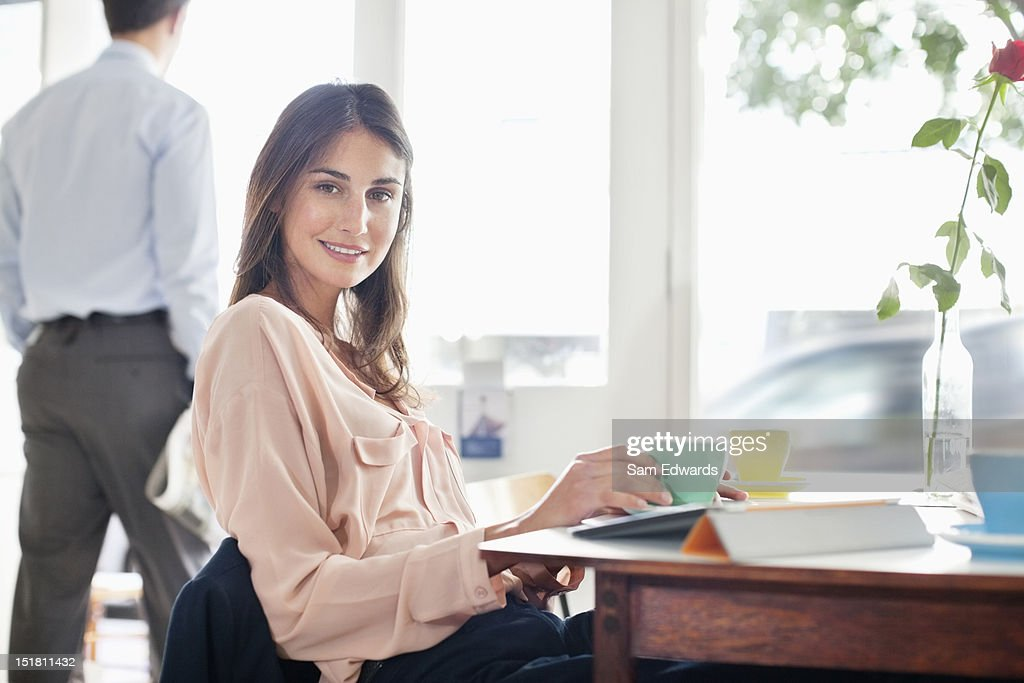 Portrait of smiling woman drinking coffee in cafe : Stock Photo