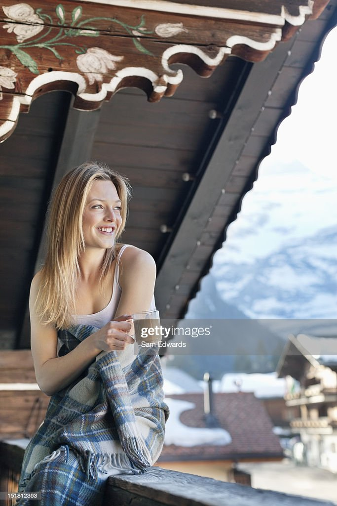 Portrait of smiling woman drinking coffee on cabin porch : Stock Photo
