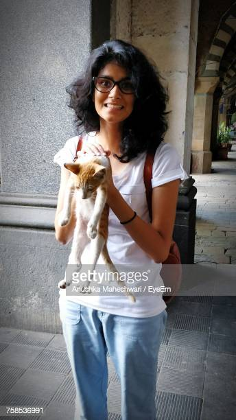 Portrait Of Smiling Woman Holding Cat While Standing Against Column