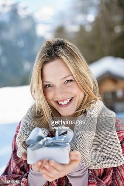 Portrait de femme souriante tenant un cadeau de Noël sous la neige