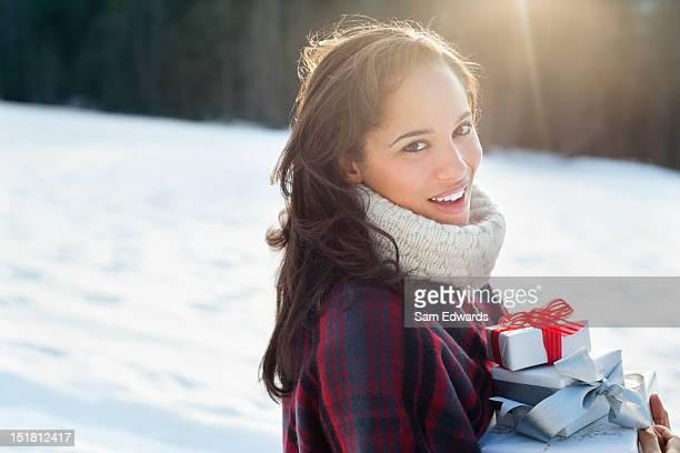 Ritratto di donna sorridente con i regali di Natale nella neve