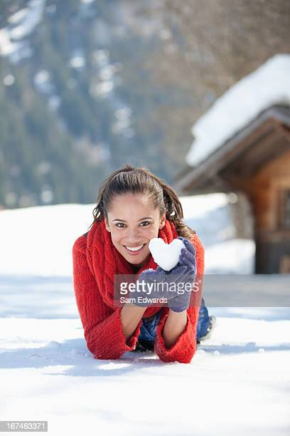 Portrait of smiling woman holding heart-shaped snowball