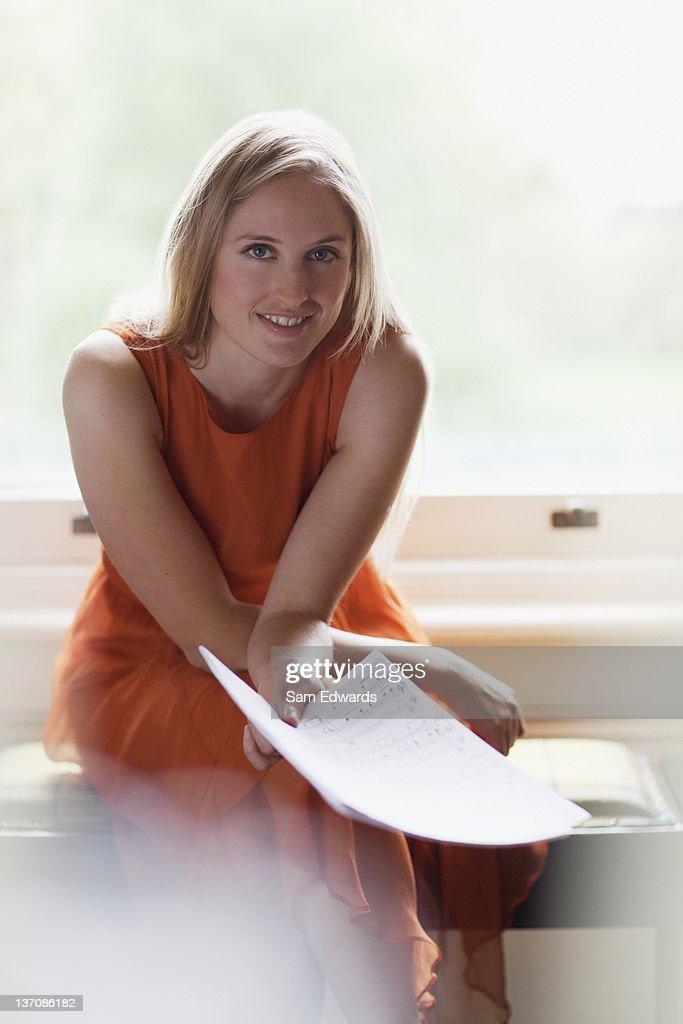 Portrait of smiling woman holding sheet music near window : Stock Photo